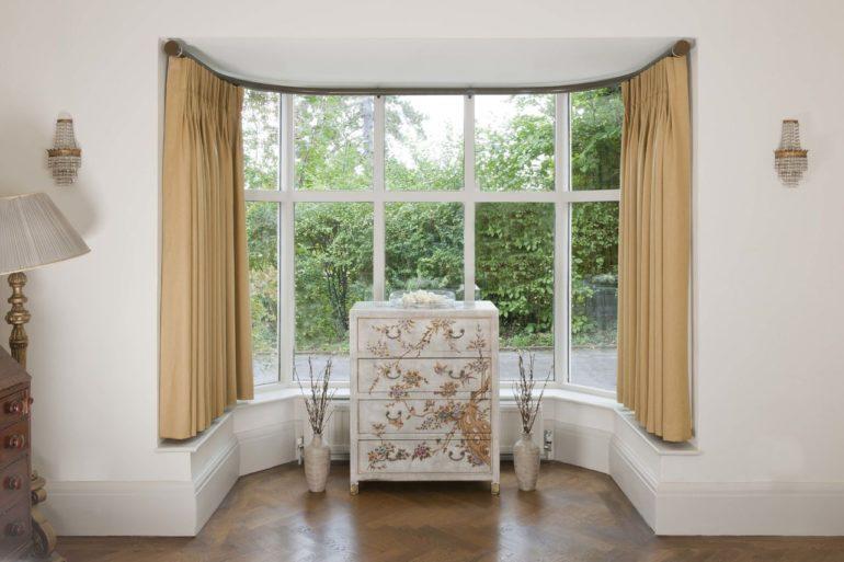 Бежевые короткие шторы это грамотное решение для оформления окна в гостиной с белыми стенами