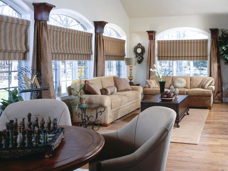 В гостиной где подход к окну закрыт мебелью короткие римские шторы придут на помощь