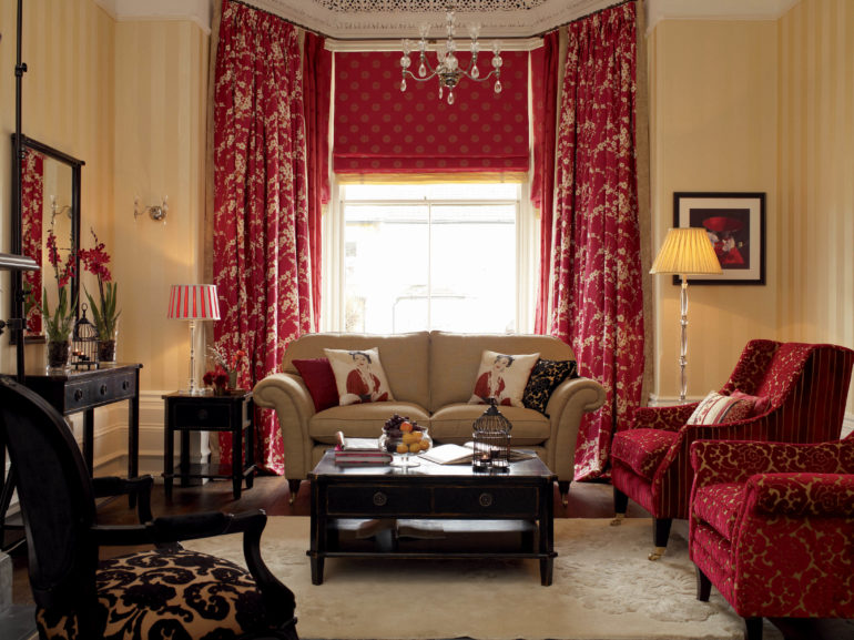 Бежевые стены и мебель внесут необходимый баланс в гостиную, где висят красные портьеры