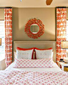 круглое зеркало в декоративной рамке над кроватью