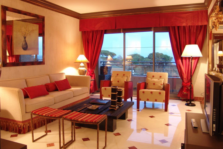 Дополняют образ красных штор такого же цвета диванные подушечки и подлокотники на креслах