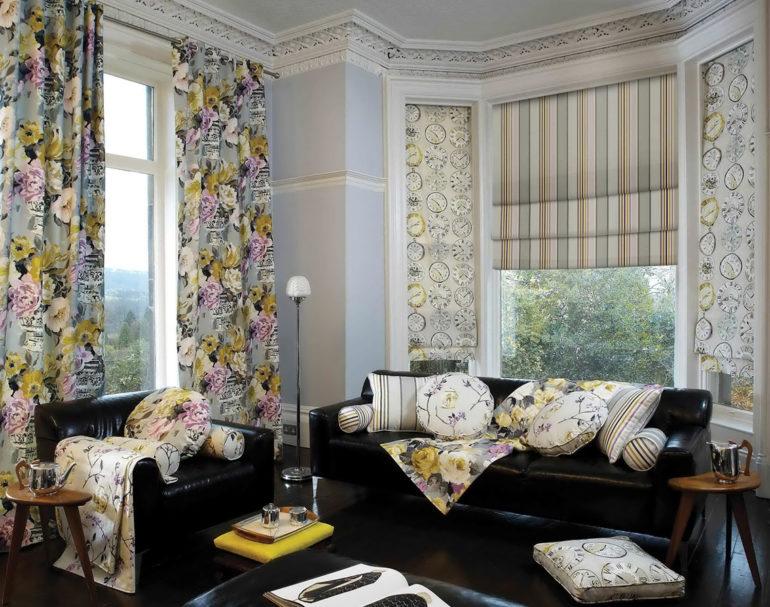 На фото в гостиной с двумя окнами сочетание классических и римских штор из габардина