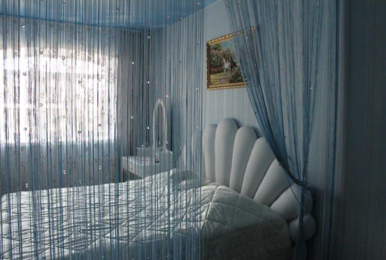 Нитяные шторы в спальне могут не быть использованы не только на окнах, но и в качестве зонирования спального места