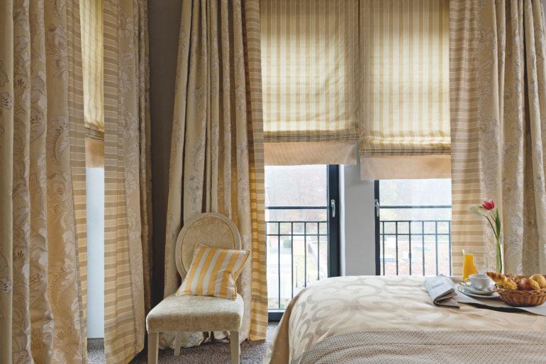 В спальню в классическом стиле лучше вешать шторы нейтральных тонов