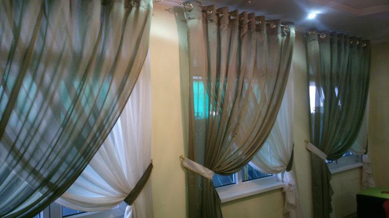На фото скрещенные шторы сшиты вместе в верхней части и закреплены на карнизе люверсами