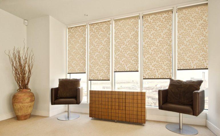 К однотонным стенам в гостиной подойдут ролеты похожего оттенка с более контрастным рисунком