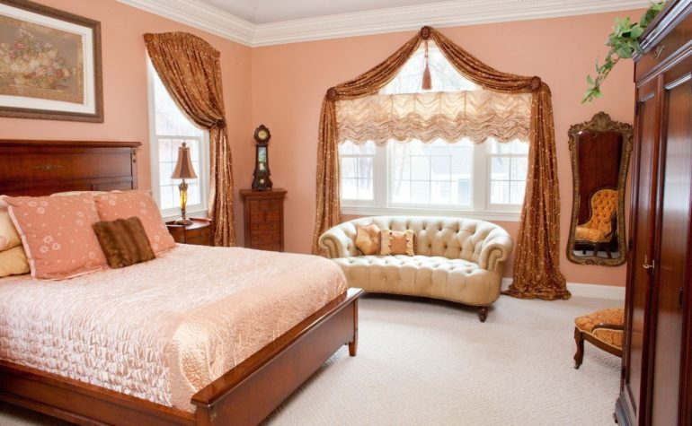 В спальне как никогда актуальны подъемные шторы - французские на данном фото отлично вписываются в классический интерьер